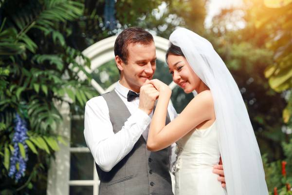handsome-caucasian-groom-is-holding-and-kissing-asian-bride-hand-with-love-and-smiling-face-during_t20_VWv7P3