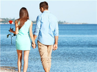Young couple with red rose walking on beach