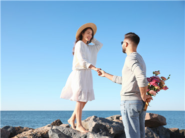 Young man giving flowers to his wife at beach. Honeymoon trip